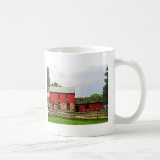 Granero rojo con la cerca tazas de café