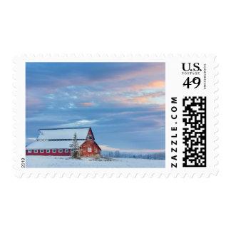 Granero rojo de madera viejo en el valle más bajo sello postal