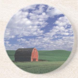 Granero rojo en campo del trigo y de la cebada en  posavasos de arenisca