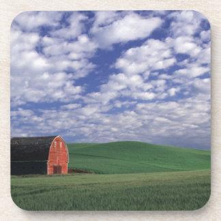 Granero rojo en campo del trigo y de la cebada en  posavasos de bebida