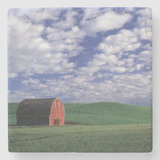 Granero rojo en campo del trigo y de la cebada en  posavasos de piedra