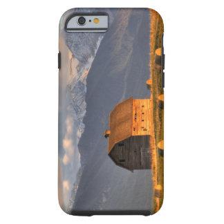 Granero viejo enmarcado por las balas de heno y funda resistente iPhone 6