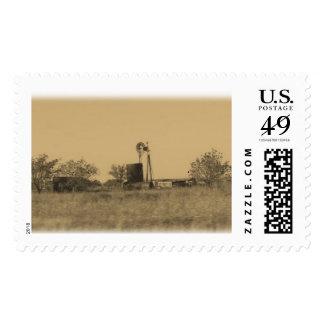 Granja occidental vieja con la bomba y el granero sellos