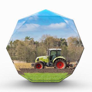 Granjero en el tractor que ara el suelo arenoso en