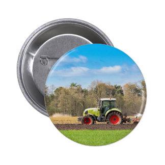 Granjero en el tractor que ara el suelo arenoso en pin redondo de 2 pulgadas