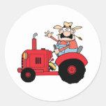 Granjero feliz en el tractor rojo que agita un pegatinas redondas