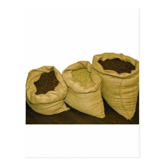 granos de café en saco de la arpillera postales