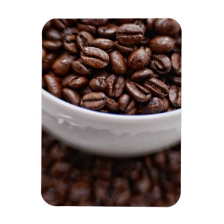 Granos de café en una taza blanca imán