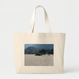 Grasshopper against the sun large tote bag