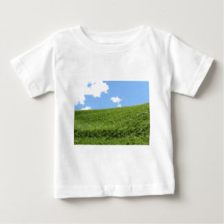 Grassy field at the rolling hill against the sky baby T-Shirt