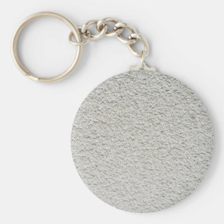 Gray wall closeup uneven granular cement coating basic round button keychain