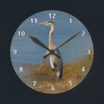 "Great Blue Heron Bird at the Pond Round Clock<br><div class=""desc"">Standing close to four feet high, the Great Blue Heron (Ardea herodias) is one of the most majestic of birds. He makes a colorful nature lover's image as he watches for a fish to swim by in the marshy pond. He has colorful blue, gray, and light brown feathers, yellow eyes...</div>"