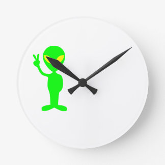 green alien clock giving the peace sign