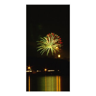 Green and red fireworks explode over the river card