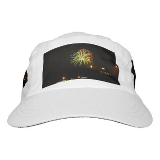 Green and red fireworks explode over the river headsweats hat
