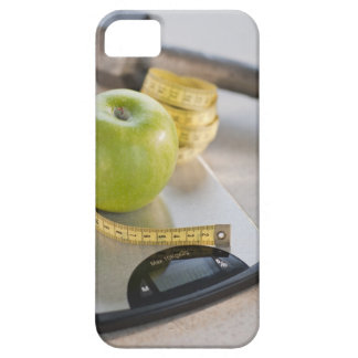 Green apple on weight scale tape measure and iPhone 5 case