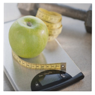 Green apple on weight scale, tape measure and ceramic tile