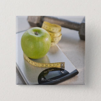 Green apple on weight scale, tape measure and pinback button