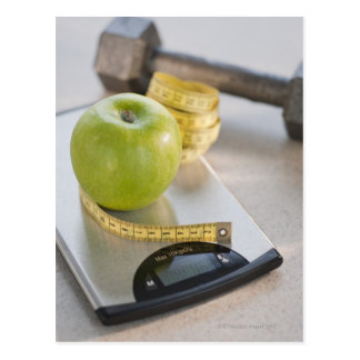 Green apple on weight scale, tape measure and postcard