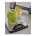 Green apple on weight scale, tape measure and poster