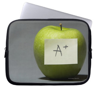 Green apple with adhesive note with letter A and Laptop Sleeve