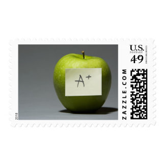 Green apple with adhesive note with letter A and Postage