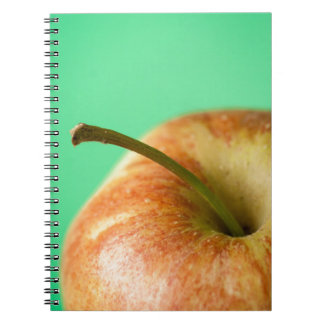 Green apple with green colored background notebook