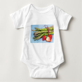 Green asparagus with strawberries on wooden baby bodysuit