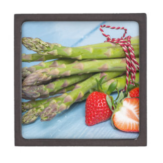 Green asparagus with strawberries on wooden jewelry box