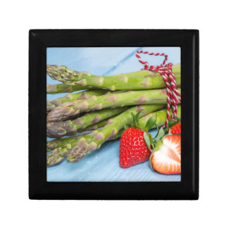 Green asparagus with strawberries on wooden keepsake box