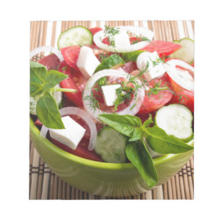 Green bowl with tasty and wholesome vegetarian notepad