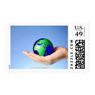 Green globe in hand postage stamp