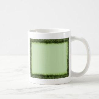 Green grass border on light green coffee mug