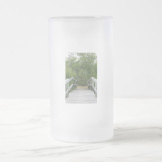 Green mangrove background, dock leading in frosted glass beer mug