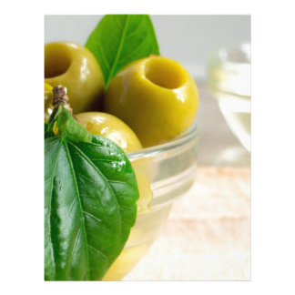 Green marinated olives pitted in a glass cup letterhead