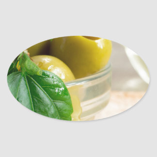 Green marinated olives pitted in a glass cup oval sticker