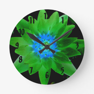 green neat water lily flower against green leaves round wall clock