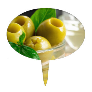 Green pickled pitted olives in a glass bowl cake topper