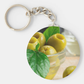 Green pickled pitted olives in a glass bowl keychain