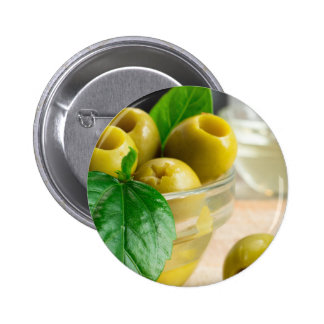 Green pickled pitted olives in a glass bowl pinback button
