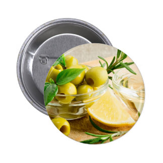 Green pitted olives decorated with herbs pinback button