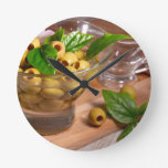 Green pitted olives in a glass cup round clock
