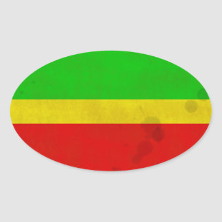 Green, yellow, and red with water stains oval sticker