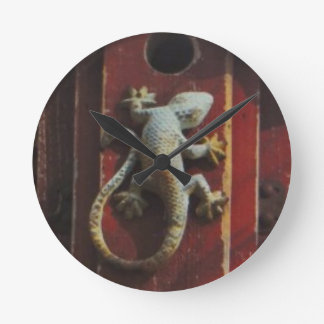 grey lizard on worn wood round clock