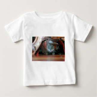 Grey tabby cat crouching under wooden table t-shirts
