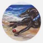 Greyhound by the sea round stickers