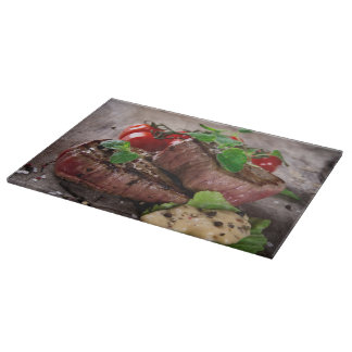 Grilled bbq steaks with fresh herbs and tomatoes cutting board
