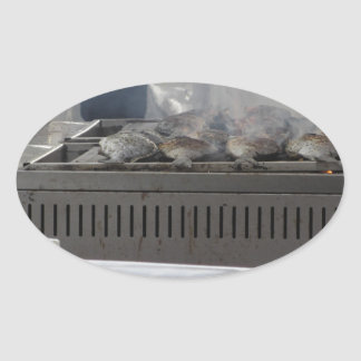 Grilling fish outdoors oval sticker