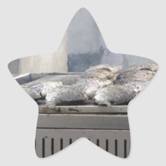 Grilling fish outdoors with smoke emerging star sticker
