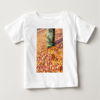 Ground around tree trunk covered with autumn leave baby T-Shirt
